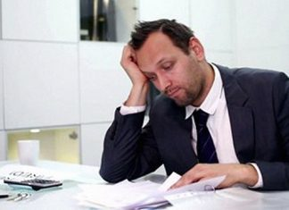 Young businessman in office being overwhelmed by too much paperwork